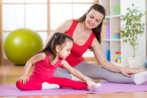 Mother and child daughter doing yoga exercises on mat at home