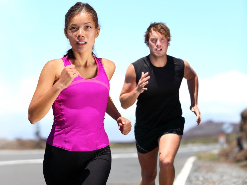 woman and man jogging on road outside. Athletic female runner and male fitness model running at speed. Young Caucasian man and beautiful Asian woman in nature.